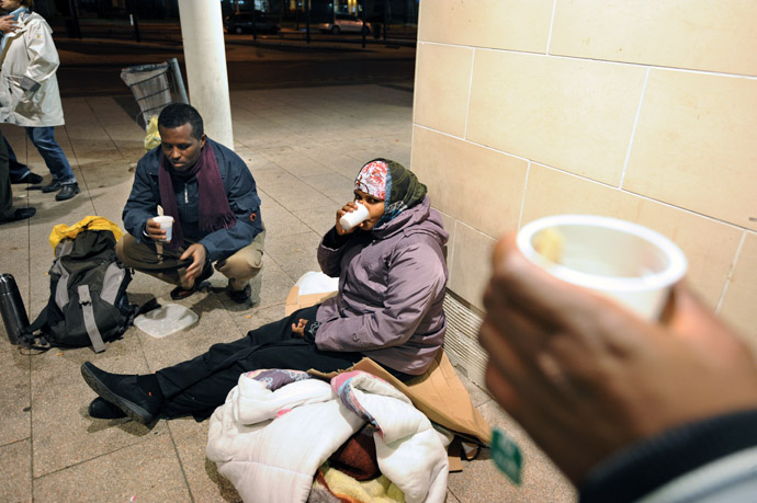 Migrants seeking asylum in France, hold drinks as they prepare to spend a night outside the railway station in Angers, centre France. (AFP Photo)