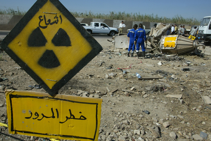 Greenpeace activists stand in front of a uranium oxide mixing vat outside the grounds of the Tuwaitha nuclear facility, 30 kms south of Baghdad, where it was allegedly dumped after being stolen by looters 24 June 2003 (AFP Photo / Cris Bouroncle)