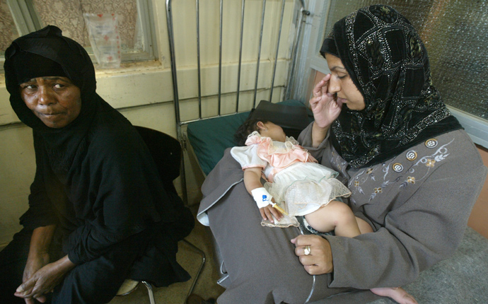 A woman sits in a ward of a hospital in Baghdad, 23 April 2003, holding her small girl ailing from gastroenteritis, in what local doctors believe is the beginning of an epidemic, mainly due to water contamination and rotting food mainly due to electricity blackouts (AFP Photo / Cris Bouroncle)