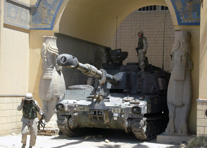 A US soldier stands on a Bradley tank stationed at the main enterance of the National Museum as another soldier walks by in Baghdad 21 June 2003. (AFP Photo)