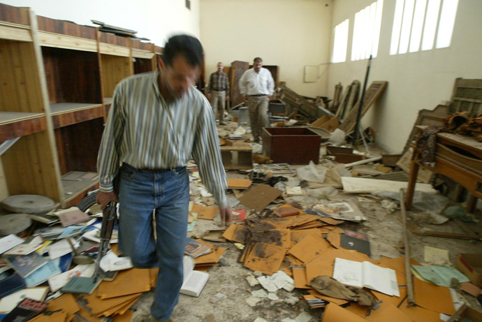 Iraqi guards walk in the ransacked and looted Iraq's largest archeological museum in Baghdad, 13 April 2003. (AFP Photo)