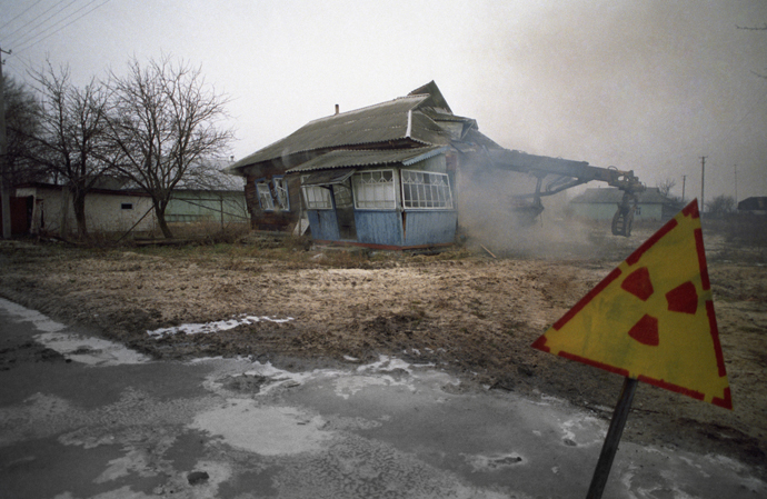 An abandoned village in the Chernobyl area is torn down because of excessive radiation. (RIA Novosti / Igor Kostin)