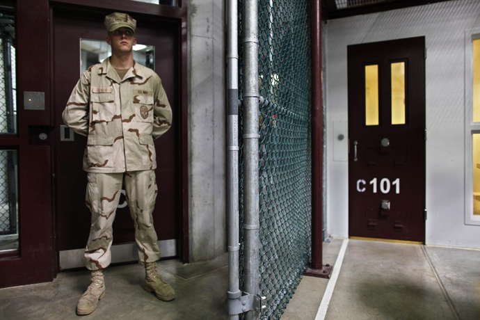 A Guantanamo guard stands inside a doorway at Camp 6 detention facility at Guantanamo Bay U.S. Naval Base, Cuba. (AFP Photo / Brennan Linsley)