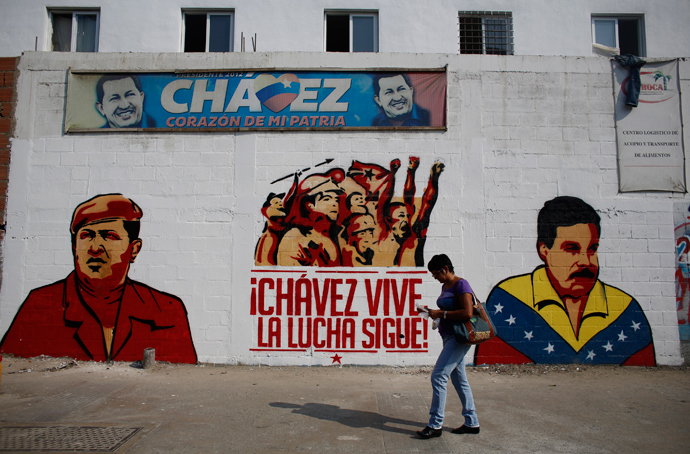 A woman walks past a mural depicting Venezuela's acting President and presidential candidate Nicolas Maduro (R) and Venezuela's late President Hugo Chavez in Caracas April 12, 2013 (Reuters / Tomas Bravo)