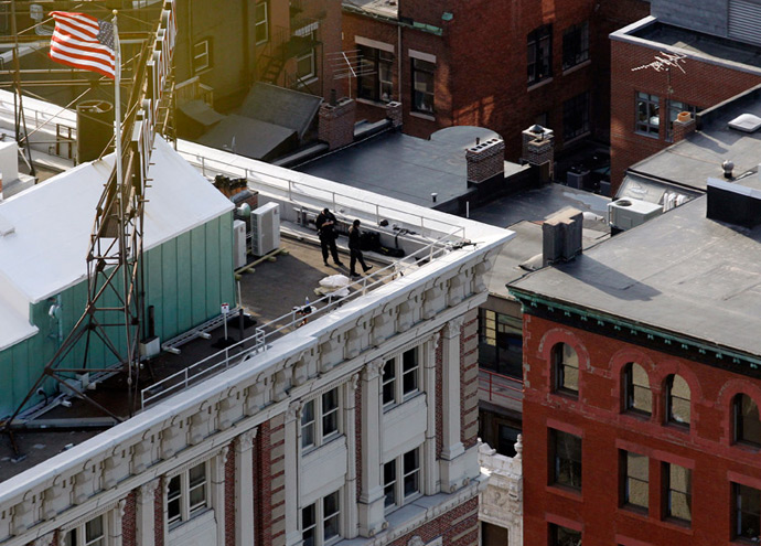 Police are seen on the roof of a building overlooking Boylston Street where explosions went off at the 117th Boston Marathon in Boston, Massachusetts April 15, 2013 (Reuters / Jessica Rinaldi)