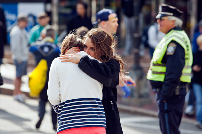 A woman comforts another, who appears to have suffered an injury to her hand, after explosions interrupted the 117th Boston Marathon in Boston, Massachusetts April 15, 2013 (Reuters / Dominick Reuter)