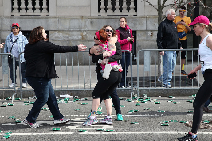 A runner embraces another woman on the marathon route near Kenmore Square after two bombs exploded during the 117th Boston Marathon on April 15, 2013 in Boston, Massachusetts (Reuters / Alex Trautwig)