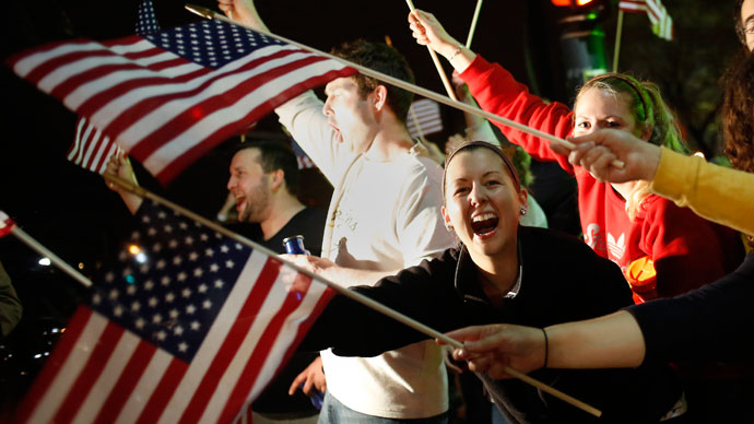 People wave U.S. flags while cheering as police drive down Arlington street in Watertown, Massachusetts April 19, 2013.(Reuters / Shannon Stapleton)