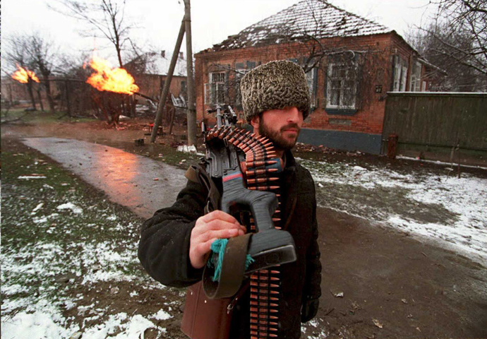 RUSSIAN FEDERATION, GROZNY: A Chechen fighter carrying a machine gun heads for downtown Grosny 17 January, 1995, as fierce fighting continue (AFP Photo)