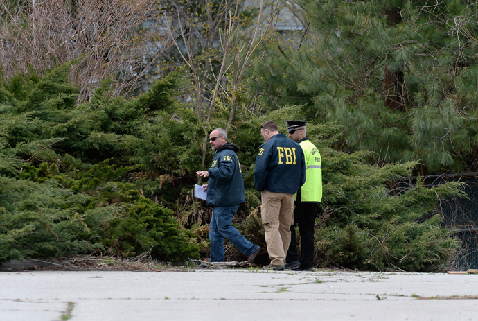 FBI investigators and Watertown Police officer walk in parking lot as they investigate the shooting scene near the boat where bombing suspect was hiding from police on Franklin Street on April 20, 2013 in Watertown, Massachusetts (Reuters / Kevork Djansezian)