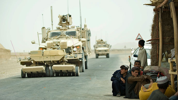Afghani men gather near the road as a military convoy by soldiers from the 1st Platoon, 1-64 Armoured Batallion, US Army - operating under NATO - roll-past security patrols at Morghan-Kecha village in Daman district, Kandahar.(AFP Photo / Tony Karumba)