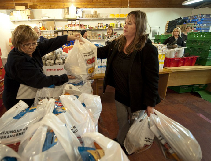 Iris Aegisdottir gets bags of food on March 3, 2010 in a warehouse in Reykjavik, where up to 550 families queue every week to receive free food from the Icelandic Aid to Families organization. (AFP Photo / Halldor Kolbeins)
