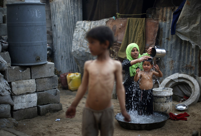 A Palestinian woman bathes her son near their dwelling on a hot day in Beit Lahiya, near the border between Israel and northern Gaza Strip April 7, 2013. (Reuters)