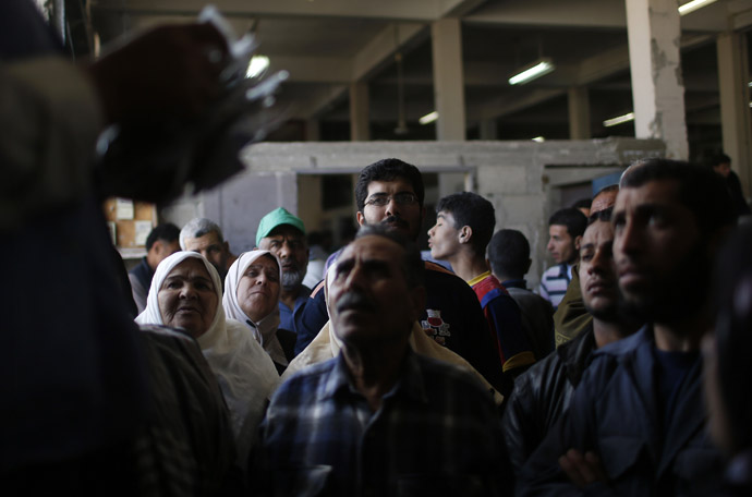 Palestinians wait to receive food supplies inside a United Nations food distribution centre in Gaza City April 10, 2013. (Reuters)