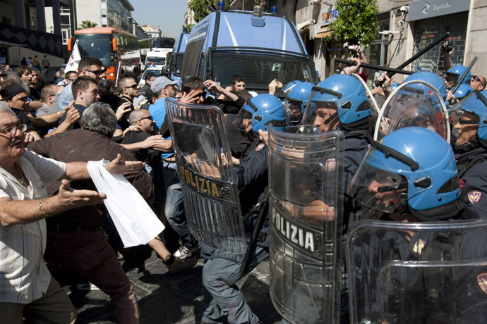 Demonstrators (L) face riot policemen as they try to enter the offices of Equitalia, Italy's tax collection agency during a protest against the government's austerity measures and the wave of suicide committed by businessmen because of the crisis inin Naples. (AFP Photo)