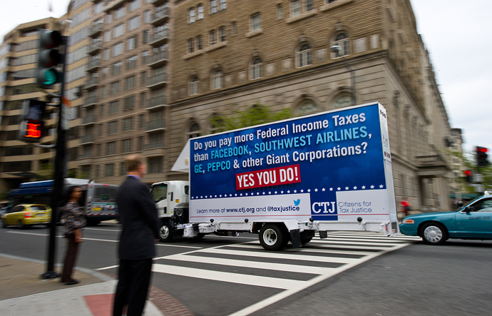 "A rolling billboard sponsored by Citizens for Tax Justice (CTJ), reading: ""Do you pay more Federal Income Taxes than Facebook, Southwest Airlines, GE, Pepco and other Giant Corporations? Yes You Do!"" A CTJ report, ""Ten Reasons We Need Corporate Tax Reform,"" crosses an intersection in Washington, DC (AFP Photo / Karen Bleier)"