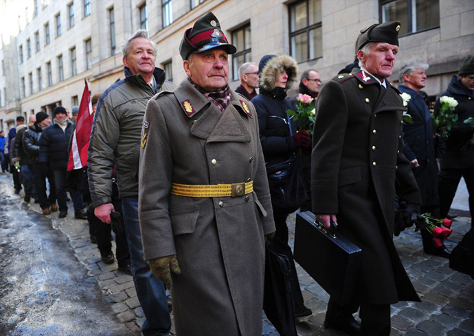Two man dressed in pre-WWII Latvian military uniforms walk along with veterans of the Latvian Legion, a force that was commanded by the German Nazi Waffen SS, and their sympathizers to the Monument of Freedom in Riga, Latvia on March 16, 2013. (AFP Photo / Ilmars Znotins)