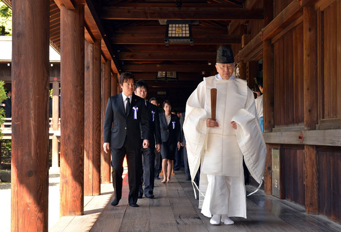 A Shinto priest (R) leads a group of Japanese lawmakers after they offered prayers for the country's war dead at the controversial Yasukuni Shrine in Tokyo on the occasion of the shrine's spring festival on April 23, 2013. (AFP Photo / Yoshikazu Tsuno)