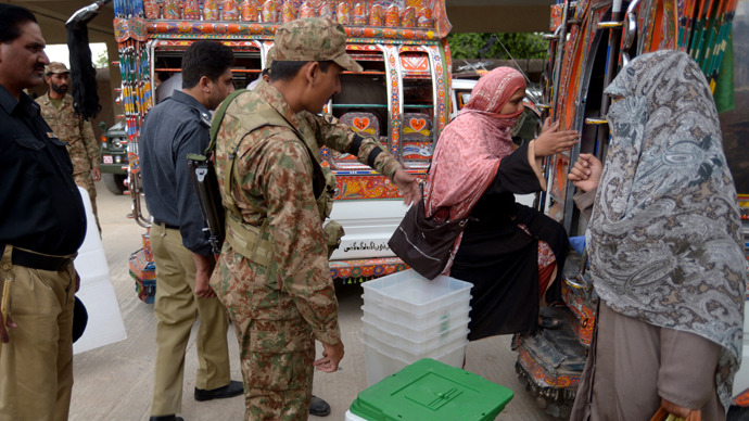 Pakistani election presiding officers (R) receive election materials at the distribution point in Rawalpindi on May 10, 2013 (AFP Photo / Farooq Naeem)