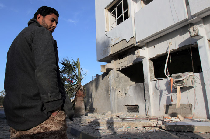Libyan security forces and bystanders walk outside a damaged police station on April 27, 2013 in Benghazi. (AFP Photo)