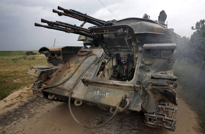 A Syrian soldier sits inside a tank as troops take control of the village of Western Dumayna, some seven kilometers north of the rebel-held city of Qusayr, on May 13, 2013.(AFP Photo / Joseph Eid)