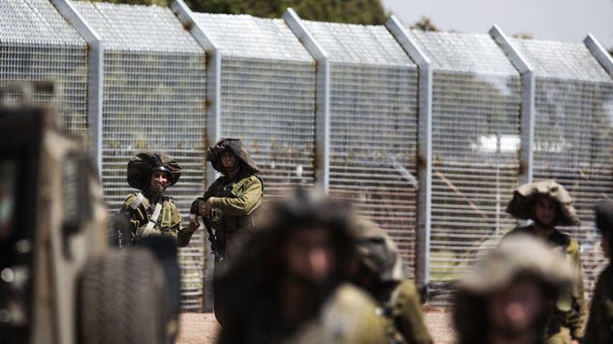 Israeliska soldater stå vakt som syriska invånare (osedda) närmar sig gränsen mellan Syrien och Israel i den israeliska fogat Golanhöjderna, nära den södra syriska byn Ar Rafide, den 7 maj 2013. (AFP Photo / Menahem Kahana)