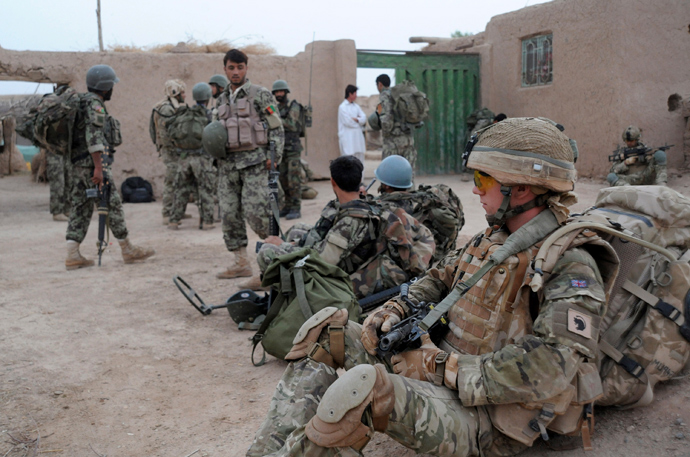 British soldiers serving with Somme Company, the 1st Battalion The Duke of Lancaster's Regiment and Afghan National Army (ANA) soldiers rest from searching for Improvised Explosive Devices (IED) in a village of Sayedebad District, Nad e Ali, Helmand Province (AFP Photo)