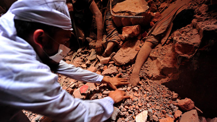 A rescue worker tries to find the remains of the garment workers, who died inside the rubble of the collapsed Rana Plaza building, in Savar, 30 km (19 miles) outside Dhaka April 25, 2013.(Reuters / Stringer)