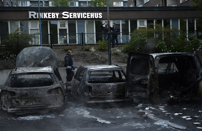 A police officers passes the scene of cars gutted by fire in the Stockholm suburb of Rinkeby after youths rioted in several different suburbs around Stockholm, Sweden for a fourth consecutive night on May 23, 2013. (AFP Photo / Jonathan Nackstrand)