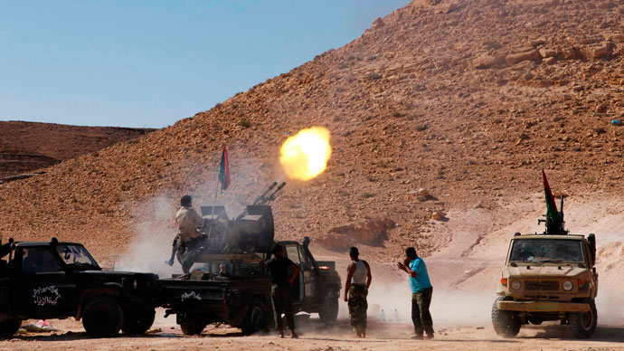 An anti-Gaddafi fighter test fires his machine gun near the frontline in the north of the besieged city of Bani Walid September 11, 2011.(Reuters / Youssef Boudlal)