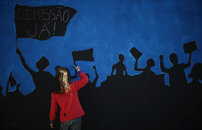 "A member of ""Damn the Troika"" movement works on a mural in Lisbon February 24, 2013. (Reuters / Rafael Marchante)"