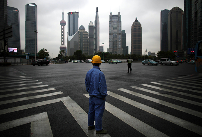 A construction worker looks at Pudong financial district as he wait to cross an avenue in Shanghai May 30, 2013. (Reuters / Carlos Barria)
