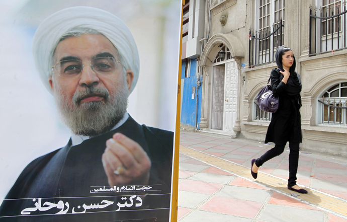 An Iranian woman walks past a campaign poster of Hassan Rowhani, moderate presidential candidate and former top nuclear negotiator, in Tehran on June 11, 2013 (AFP Photo / Atta Kenare)