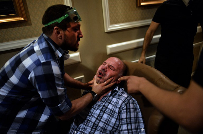 A man suffers from tear gas after being carried inside a hotel during clashes between protesters and riot police at Taksim square in Istanbul on June 11, 2013. (AFP Photo / Aris Messinis)
