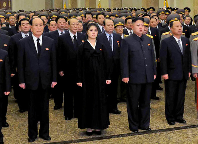 North Korean leader Kim Jong Un (centre R, front), accompanied by his wife Ro Sol Ju (centre L, front) and senior officials of the party and North Korean Army paying respect to late leader Kim Jong Il at the Kumsusan Palace in Pyongyang for the first anniversary of his death (AFP Photo / KCNA via KNS)