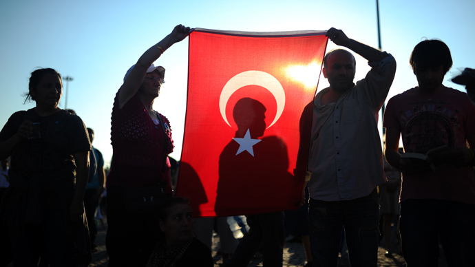 People hold a Turkish national flag as they stand on the flashpoint Taksim square in Istanbul on June 18, 2013 during a wave of new alternative protests (AFP Photo / Bulent Kilic)