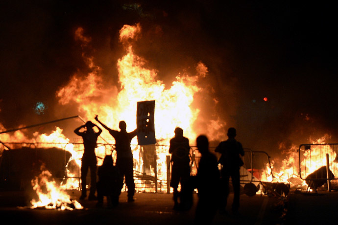 Demonstrators stand next to a fire during a protest part of what is now called the 'Tropical Spring' against corruption and price hikes, on June 20, 2013, in Rio de Janeiro. (AFP Photo)