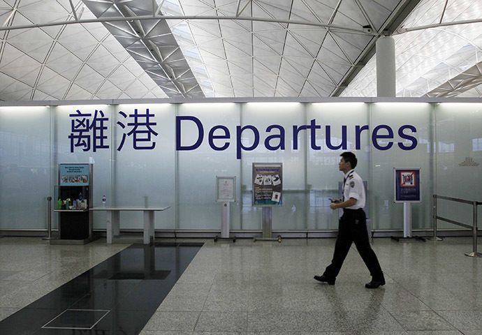 An airport security guard walks past a sign at the departure hall of Hong Kong Airport June 23, 2013. Edward Snowden, a former contractor for the U.S. National Security Agency, charged by the United States with espionage, was allowed to leave Hong Kong on Sunday, his final destination as yet unknown, because a U.S. request to have him arrested did not comply with the law, the Hong Kong government said. (Reuters / Bobby Yip)