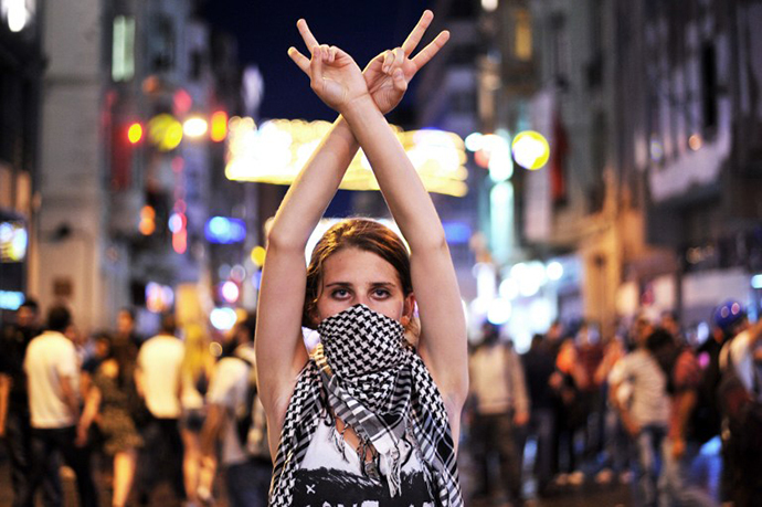 An anti goverment protester flashes a victory sign during the clashes between protestors and riot police on Taksim square in Istanbul on June 22, 2013. (AFP Photo / Ozan Kose)