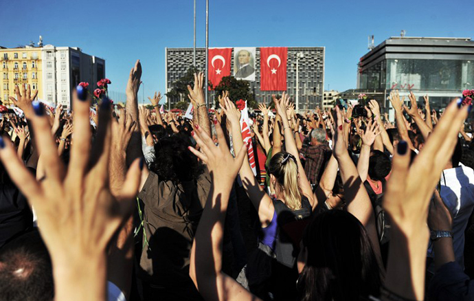 Protesters raise their hands as they gather on Taksim square during the clash between riot police and protestors in Istanbul on June 22, 2013. (AFP Photo / Ozan Kose)