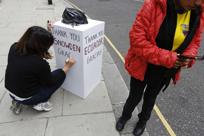 A supporter of Edward Snowden writes a message on a board outside the Embassy of Ecuador in London June 24, 2013. (Reuters)