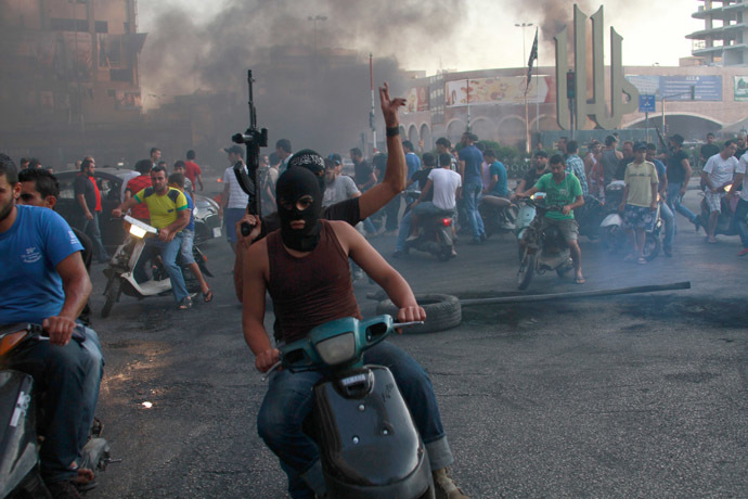 Sunni Muslim gunmen roam the streets and block roads with burning tires, expressing their solidarity with Salafist leader Ahmad al-Assir in Tripoli, northern Lebanon, June 23, 2013. (Reuters)