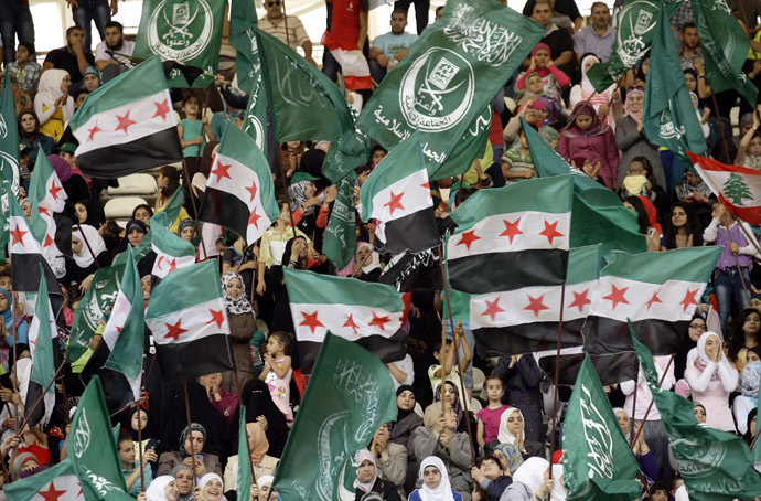 Syrians and Lebanese wave Syria's former independence flag which has been adopted by the rebels forces fighting agianst Syrian pro-government forces in Syria, and the green Sunni Muslim Jamaa Islamiya flag as they gather in the main sports stadium in the southern Lebanese city of Sidon on June 9, 2013 in solidarity with the Syrian central city of Qusayr which fell to government forces, aided by Lebanon's Hezbollah fighters, earlier in the week. (AFP Photo)