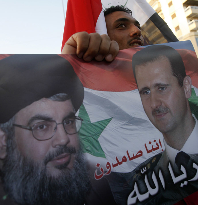 A man carries a placard bearing the portraits of Syrian President Bashar al-Assad and Hezbollah leader Hassan Nasrallah, during a gathering to celebrate the capture of the city of Qusayr by Syrian pro-government forces, in the southern Lebanese city of Sidon, on June 6, 2013. (AFP Photo)