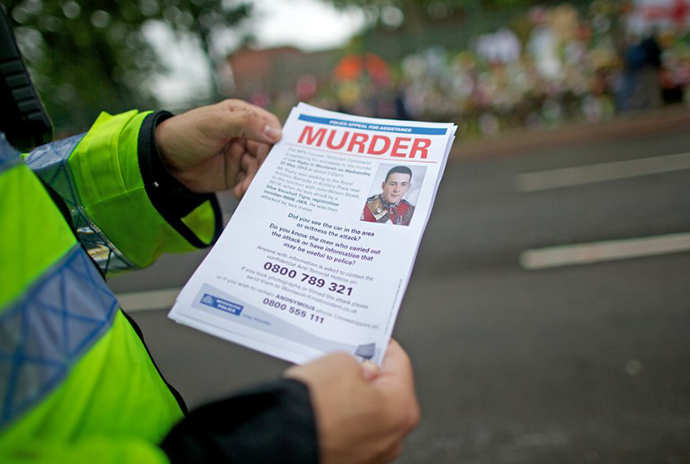 A police officer holds a leaflet requesting information about the murder of Drummer Lee Rigby of the 2nd Battalion the Royal Regiment of Fusiliers outside Woolwich Barracks in London, on May 29, 2013. (AFP Photo / Andrew Cowie)