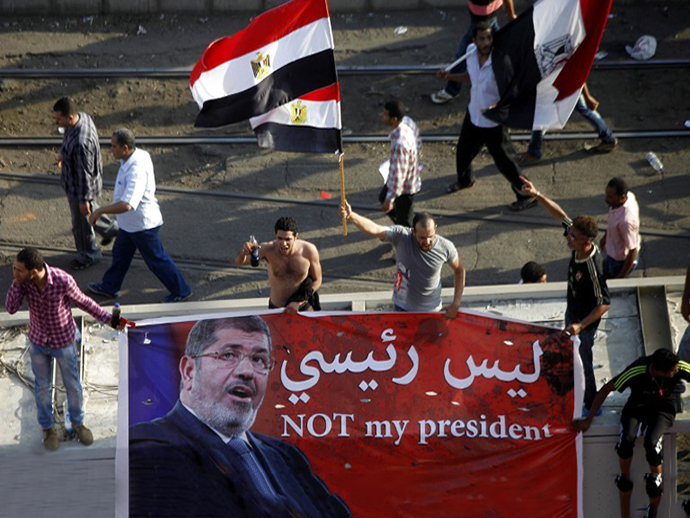 Opponents of Egypt's Islamist President Mohamed Morsi shout slogans while holding an anti-Morsi banner during a protest calling for his ouster outside the presidential palace in Cairo on June 30, 2013. (AFP Photo / Mahmud Khaled)