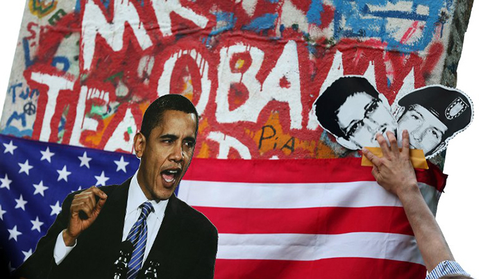 Activists display a photo of US President Barack Obama and pictures of former US spy Edward Snowden and whistleblower Bradley Manning during a protest action (AFP photo / Ronny Hartmann)
