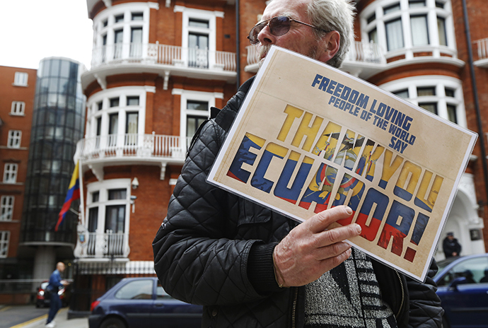 A supporter of Edward Snowden holds a sign outside the Embassy of Ecuador in London (Reuters / Luke MacGregor)