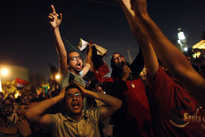 Egyptian protesters calling for the ouster of President Mohamed Morsi react as they watch his speech on a screen in a street leading to presidential palace early in Cairo on July 3, 2013.(AFP Photo / Mahmud Khaled)