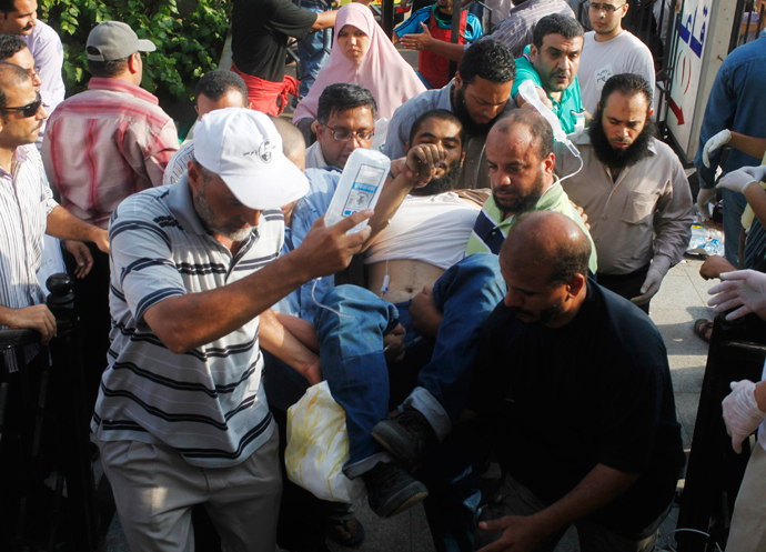 Supporters of deposed Egyptian president Mohamed Mursi help a wounded supporter outside the Republican Guard headquarters in Cairo, July 8, 2013 (Reuters / Asmaa Waguih)